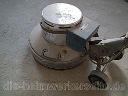 Fliesenkleber mit einer Tellerschleifmaschine entfernen.