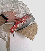 Tapete entfernen mit einem breiten Spachtel.