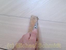 An einem Holzwinkel wird der Vinylboden von oben angeschnitten und umgeklappt.